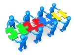 """Team Of 8 Blue People Holding Up Connected Pieces To A Colorful Puzzle That Spells Out """"Team,"""" Symbolizing Excellent Teamwork, Success And Link Exchanging Clipart Illustration Graphic"""